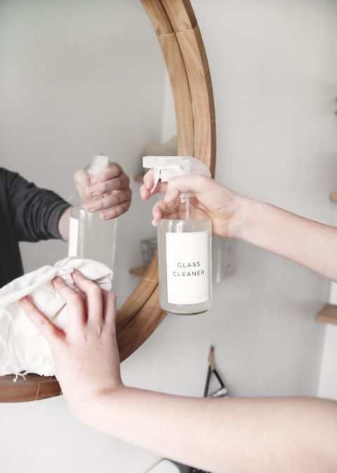 hands holding class cleaner spray bottle and rag while cleaning mirror