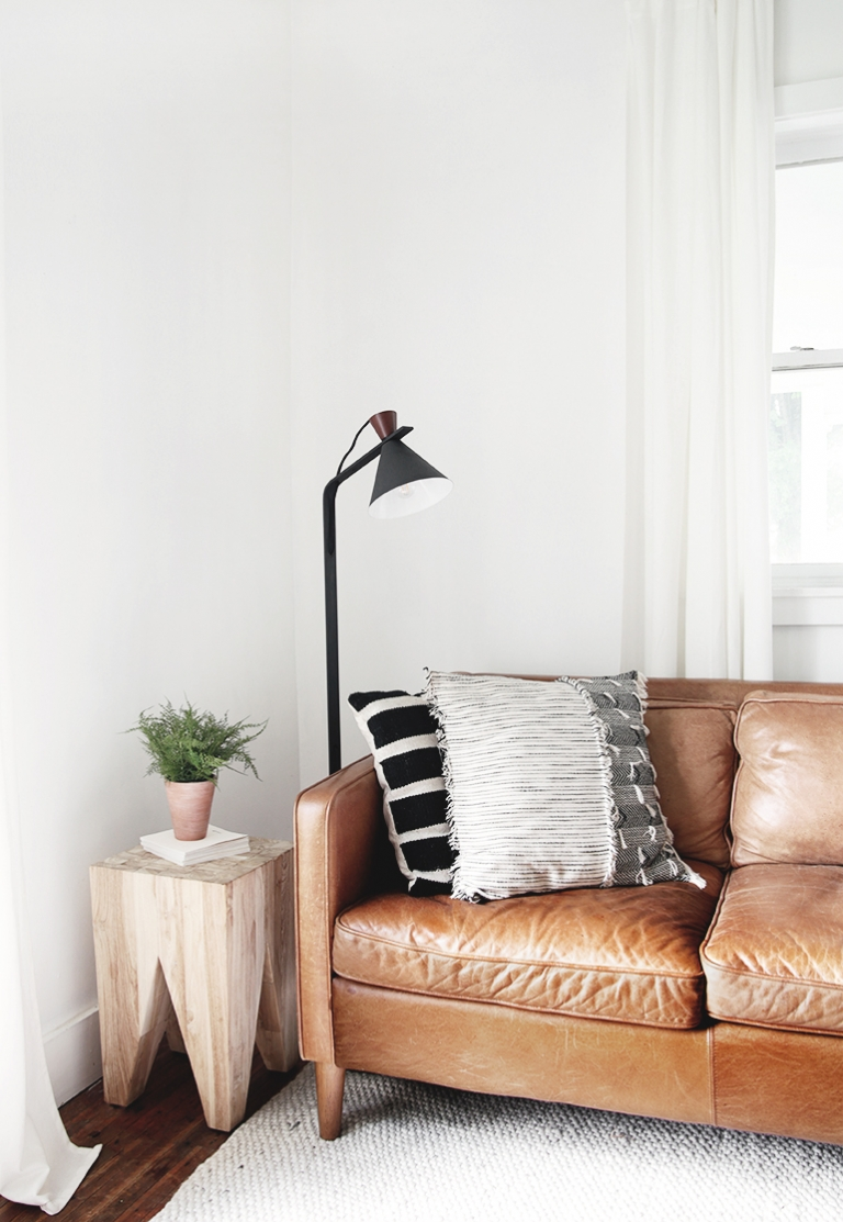 brown leather couch next to black lamp and wood side table
