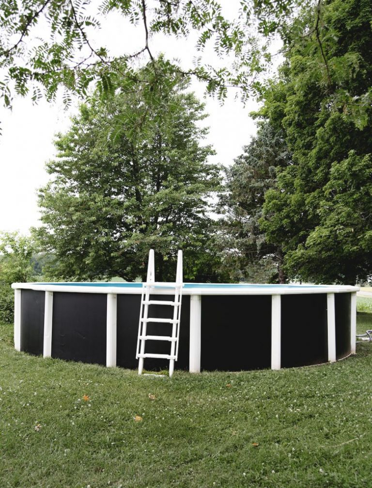 above ground pool with painted black walls with white ladder