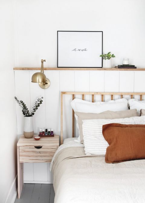 shiplap wall with brass lamp on it next to modern wood bed
