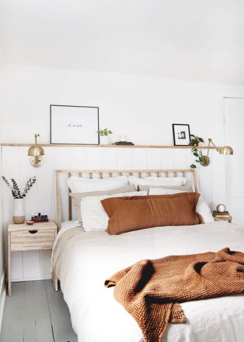 simple bedroom with linen blankets brass lamps