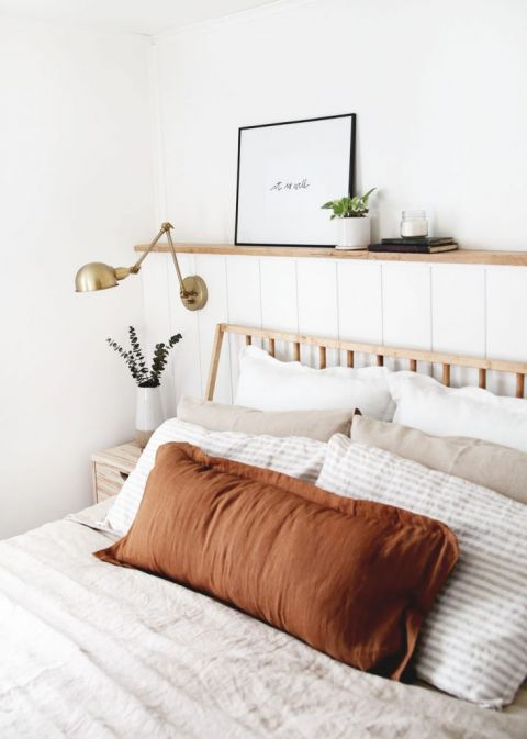 modern bedroom with rust colored pillow on bed brass lamp on wall