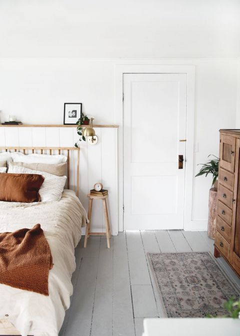 simple modern bedroom with gray painted floor and wood bed and dresser