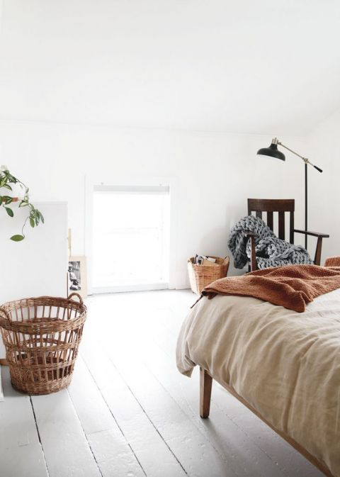 simple white bedroom with rocking chair and black floor lamp
