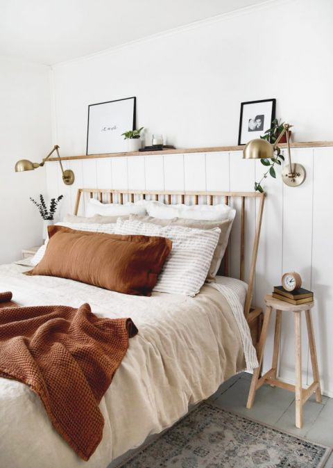 modern bed with rust blanket and brass lamp on shiplap wall