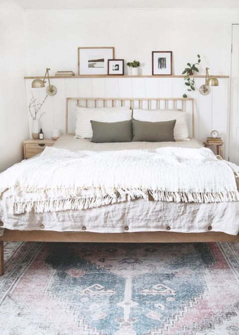 bedroom with wood dowel headboard bed and neutral vintage inspired rug